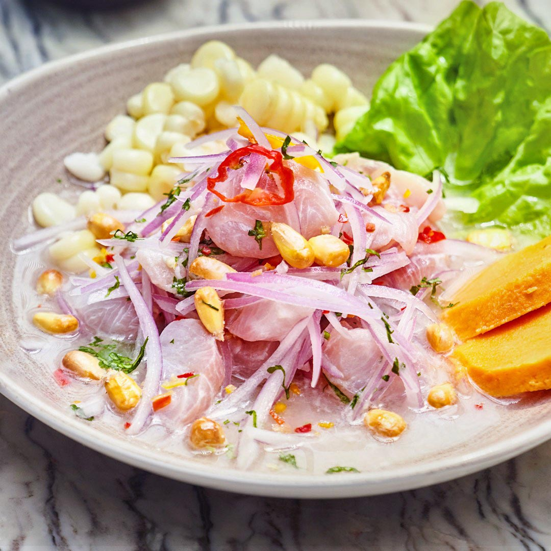 A plate of ceviche with white fish, onions, corn kernels, lettuce, and sweet potato.