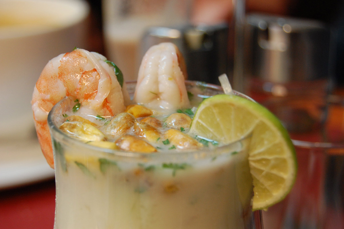 A cup of a milky liquid with shrimp, corn, cilantro, and lime on top.