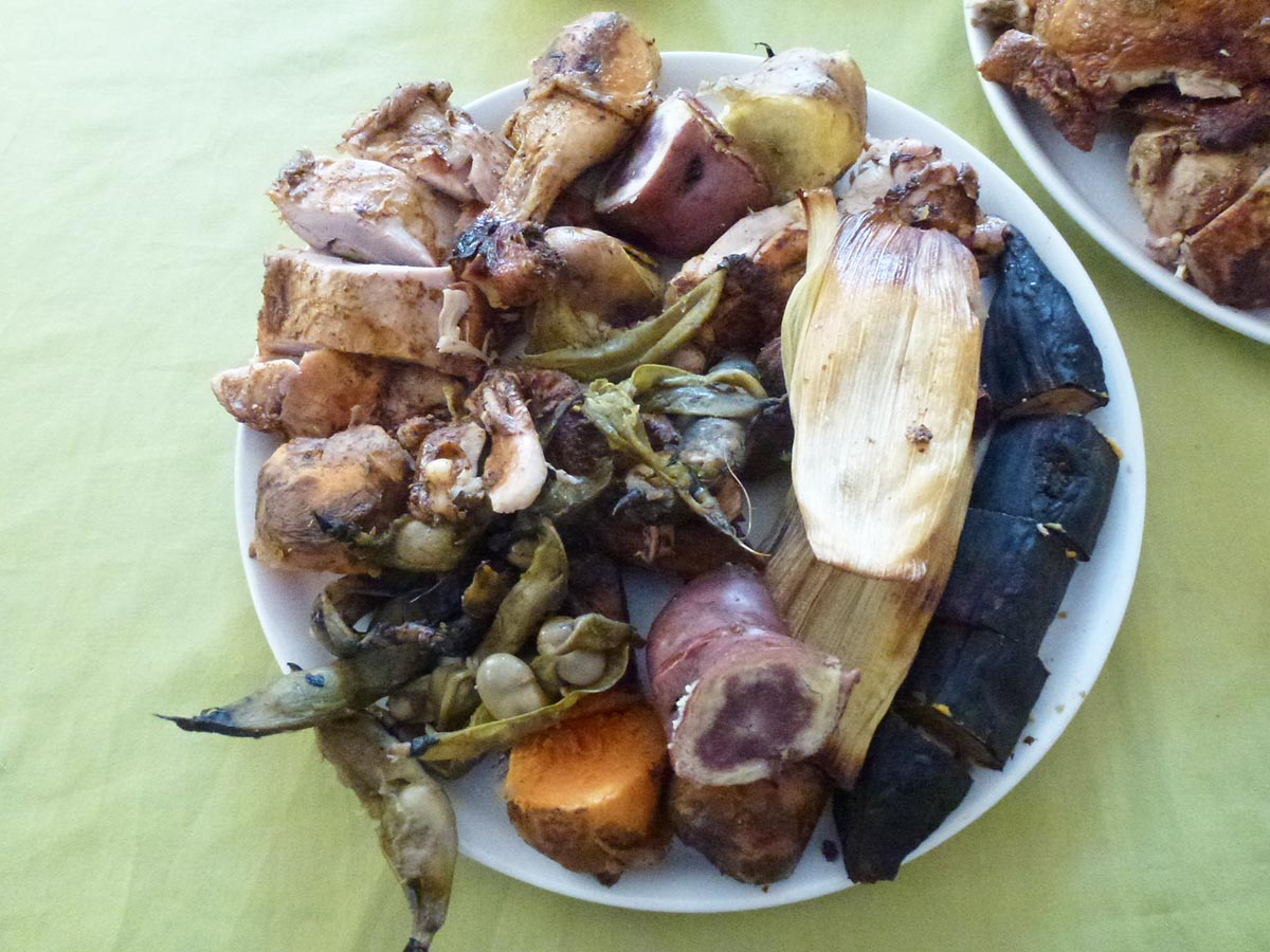 A plate full of various meats and vegetables, typical of a pachamanca meal.