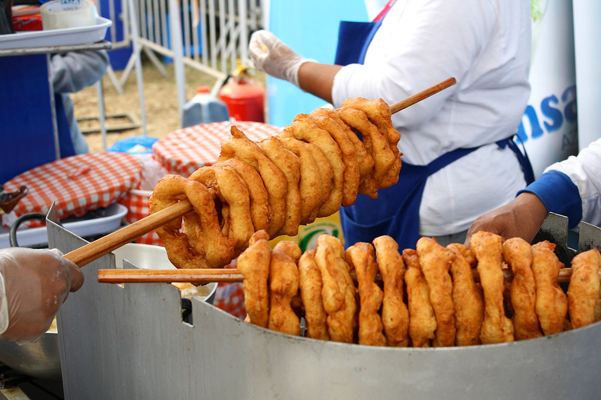 Wooden sticks with many brown doughnuts known as picarones sit above a fryer.