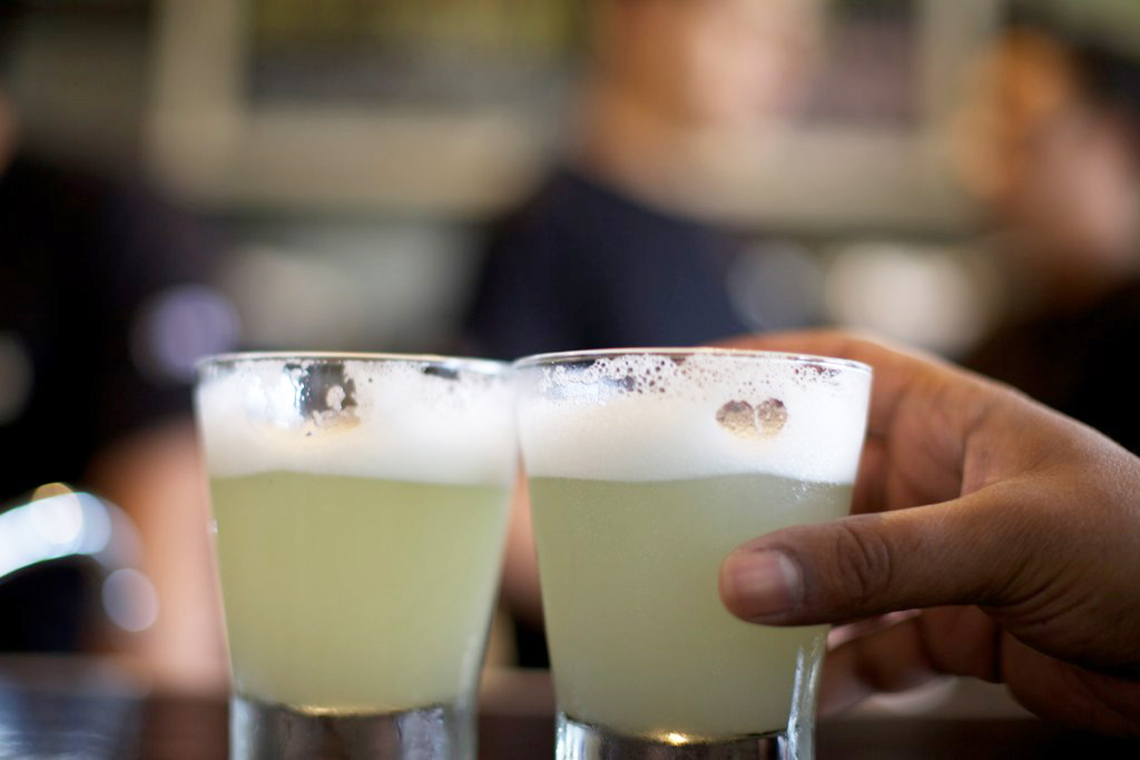Two glasses with Peru's national drink, the Pisco sour, a yellow frothy cocktail.