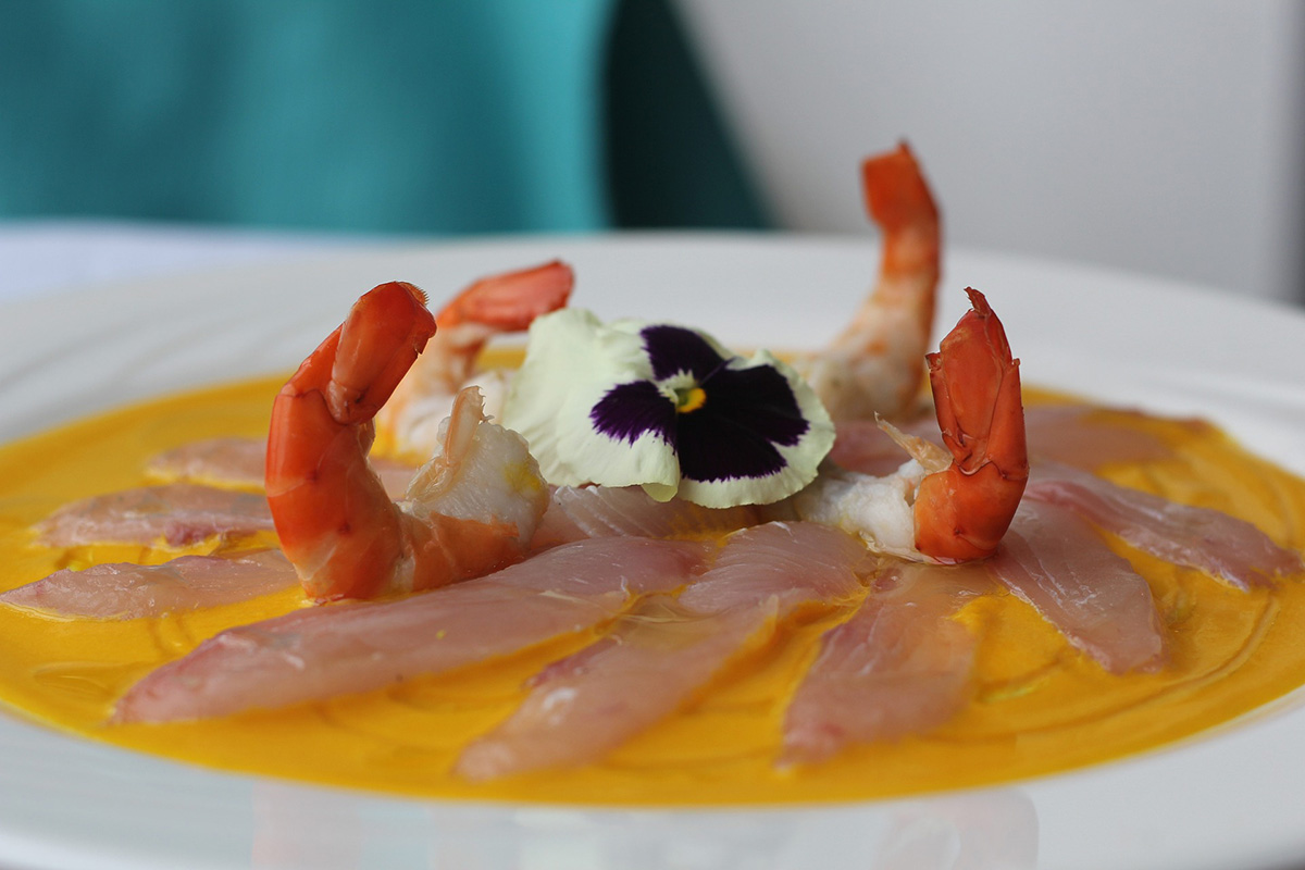 A plate of thinly slices fish with an orange citrus sauce and shrimp on top.