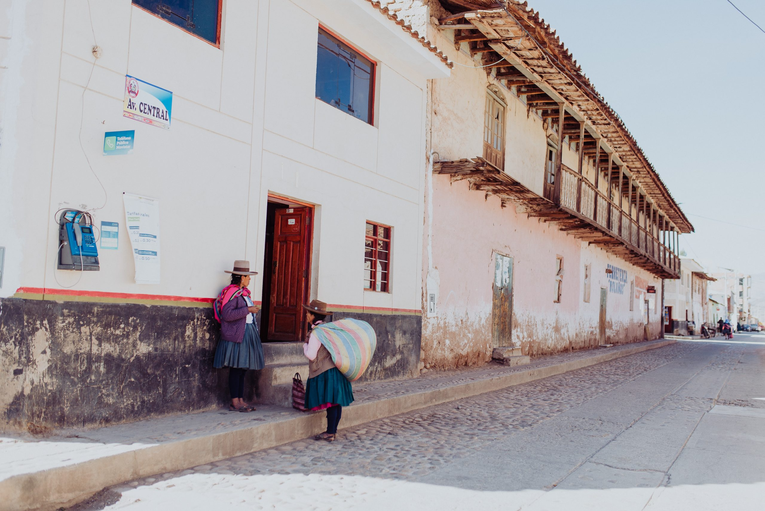 Long shot of two women of the Andes region of Peru meeting on a street, holding large bags on their back.