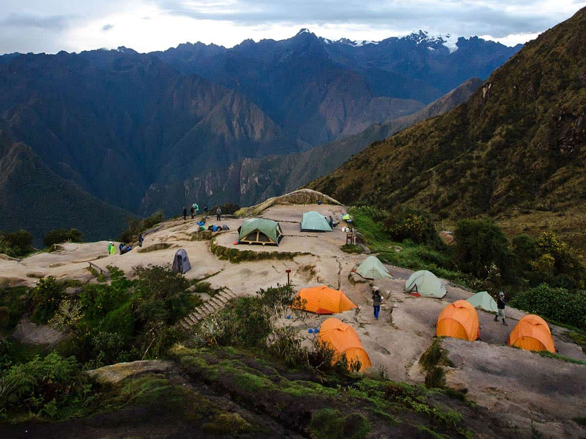 campsite with yellow and green tents overlooking mountains