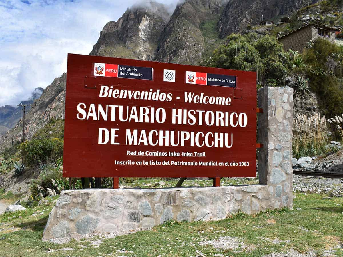 red welcome sign for the Machu Picchu Sanctuary at the start of the Inca Trail