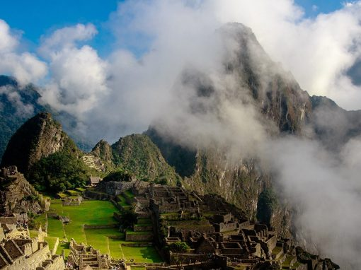 The iconic Machu Picchu ruins with the mountains behind partially covered in clouds.