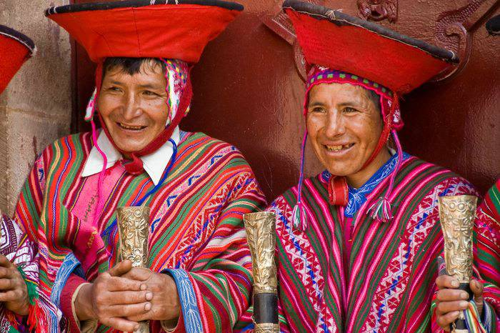 Two men dressed in intricately designed, colorful clothing with red hats holding a carved object.