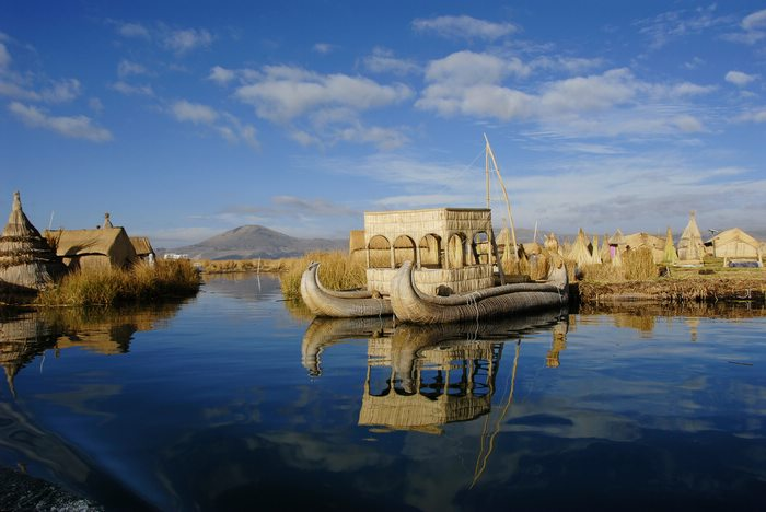 Lake reflects image of reed boat anchored next to Uros floating island