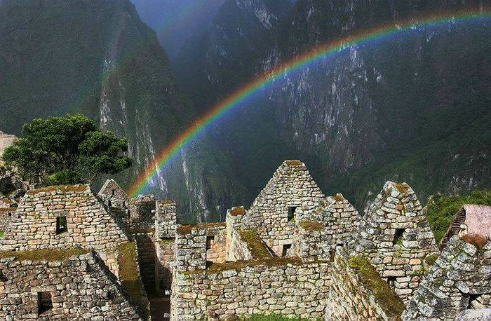 A rainbow above several walls of stone ruins at Machu Picchu.