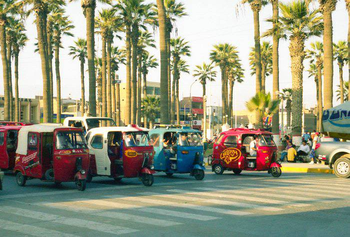 Street with a line of mototaxis parked on a sunny day with palm trees in the background