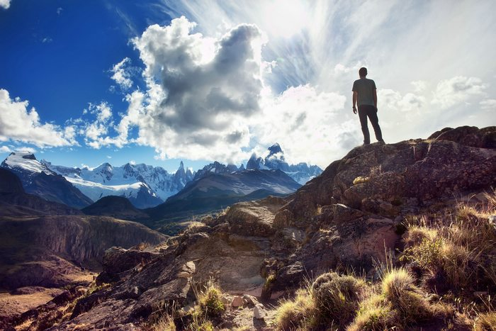 A person stands on a mound overlooking snow-capped mountains in El Chalten, Argentina.