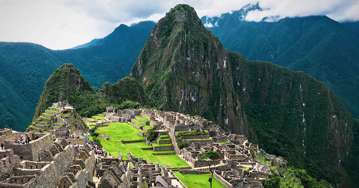 The iconic Inca ruins of Machu Picchu and surrounding mountains as seen from a lookout point.
