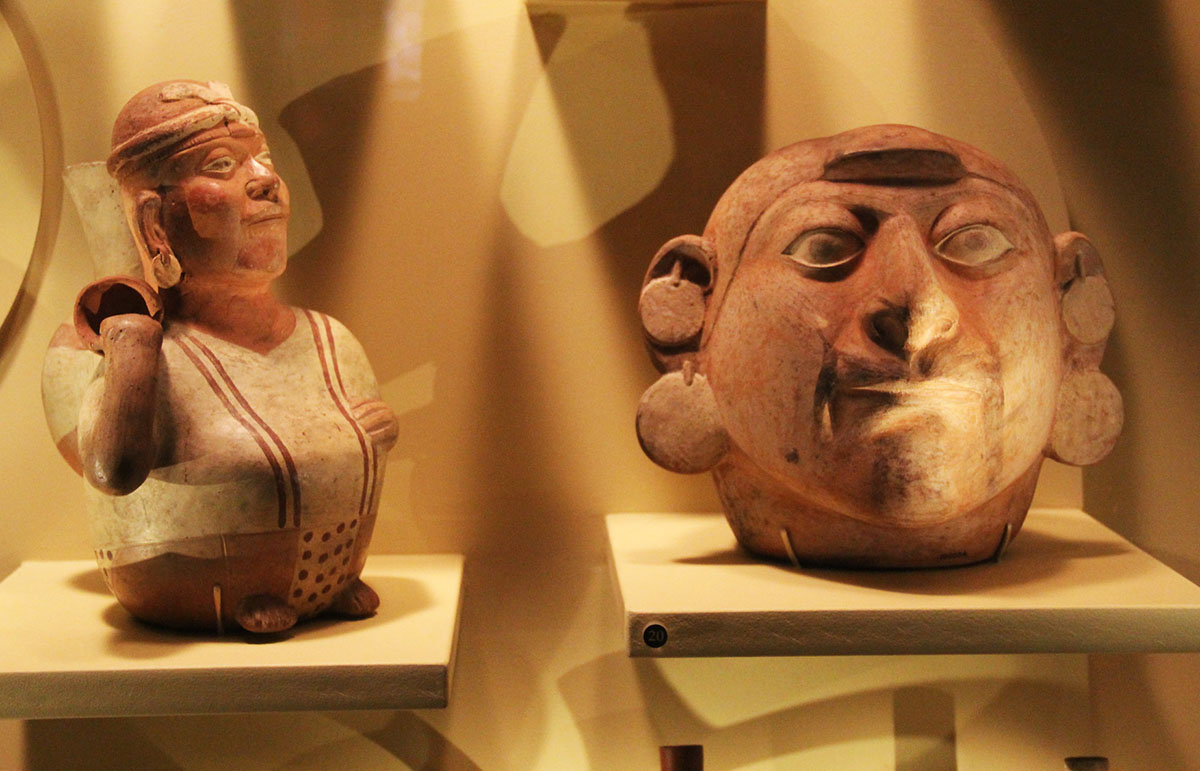Two ceramic pieces on display. One is in the shape of a human body. The other is of a human head.