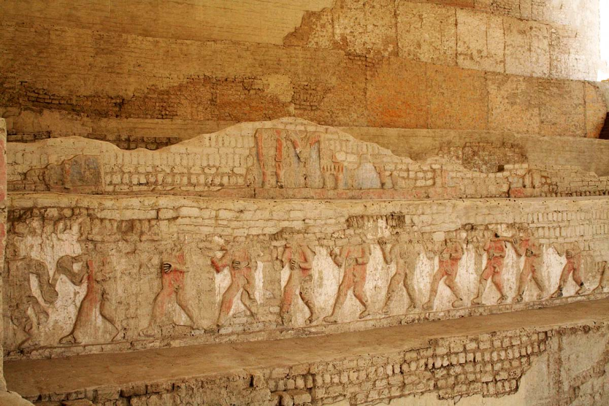 A wall carving of repeating human figures walking in unison at El Brujo.