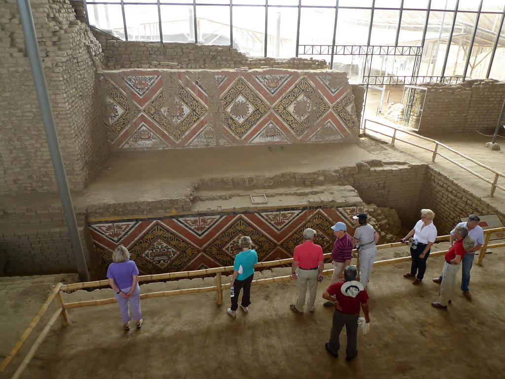 Nine visitors overlook the intricate murals of the Moche Temple of the Moon.