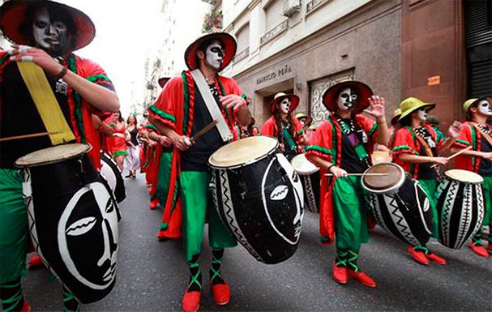 People in red, black, and green attire drumming on black and white drums in a Carnaval parade.