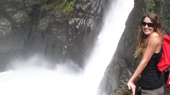 A visitor at a waterfall in Baños, Ecuador.