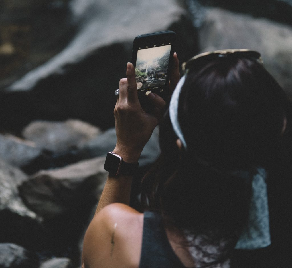A woman holding a smartphone and taking a picture of a waterfall.