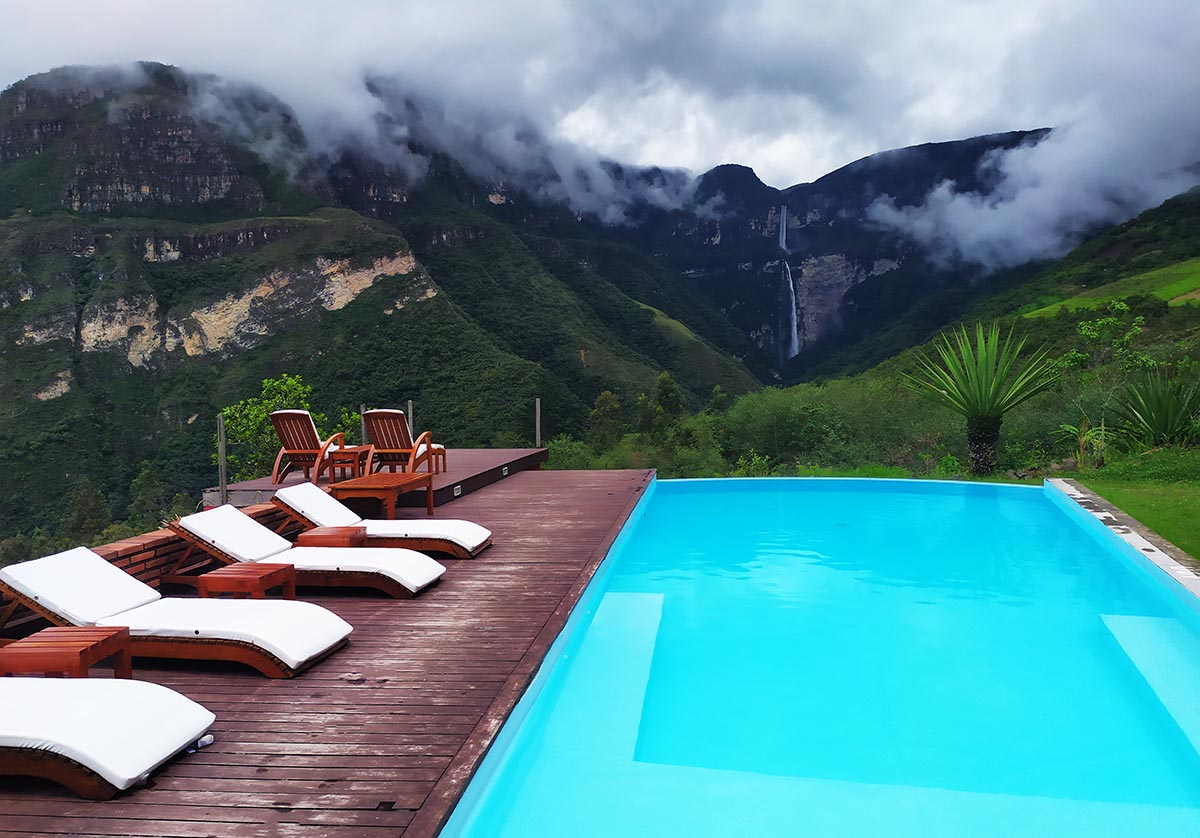 A long blue pool with lounge chairs on the side looks off towards the Gocta Waterfall in the distance.