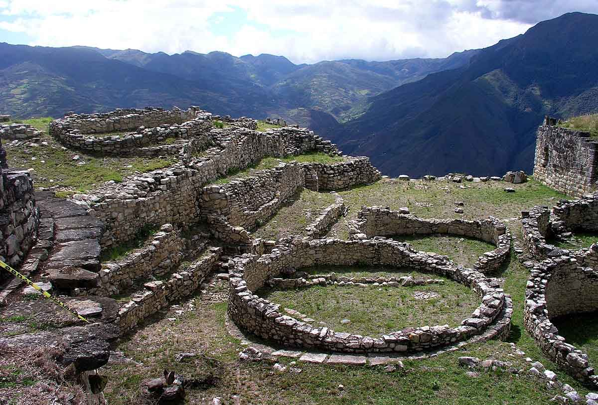 The sun shines over the stone ruins in circular shapes at Kuelap.