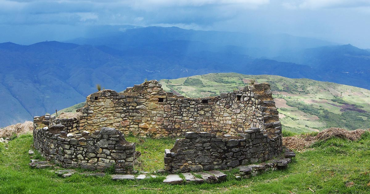 A circular stone house weathered away in time at the Kuelap Fortress in Peru.