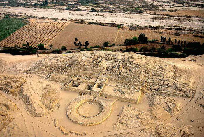 Aerial view of Caral ruins with a slight pyramid shape and circular construction in front.