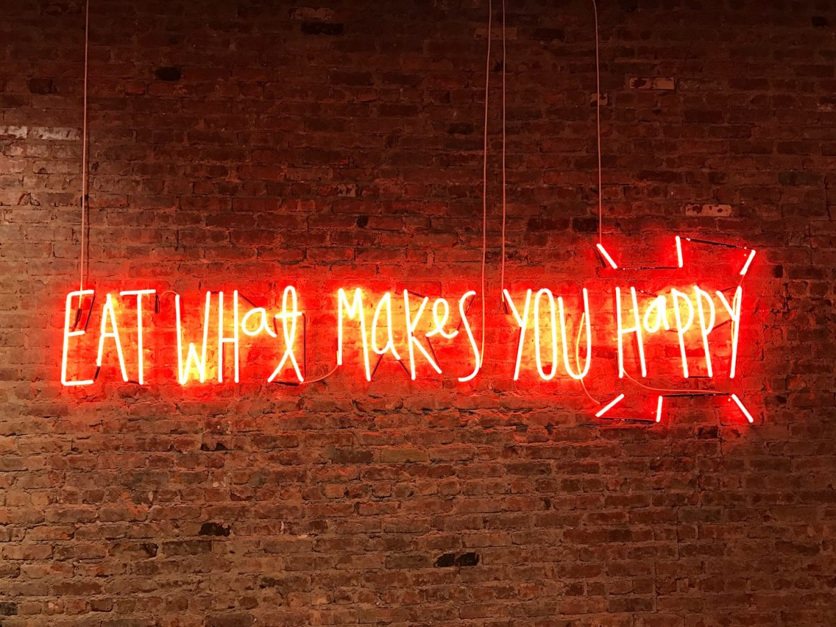 neon sign that says eat what makes you happy against a red brick wall