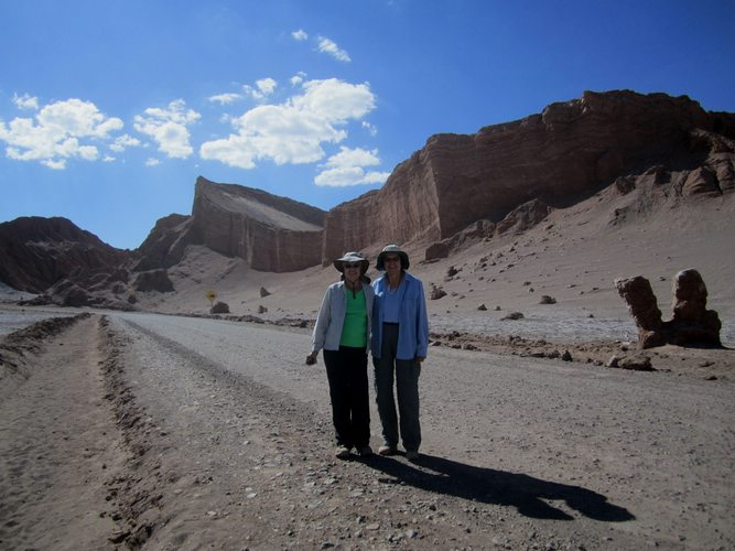 Two women stand in front of several rock formations in the Atacama Desert.