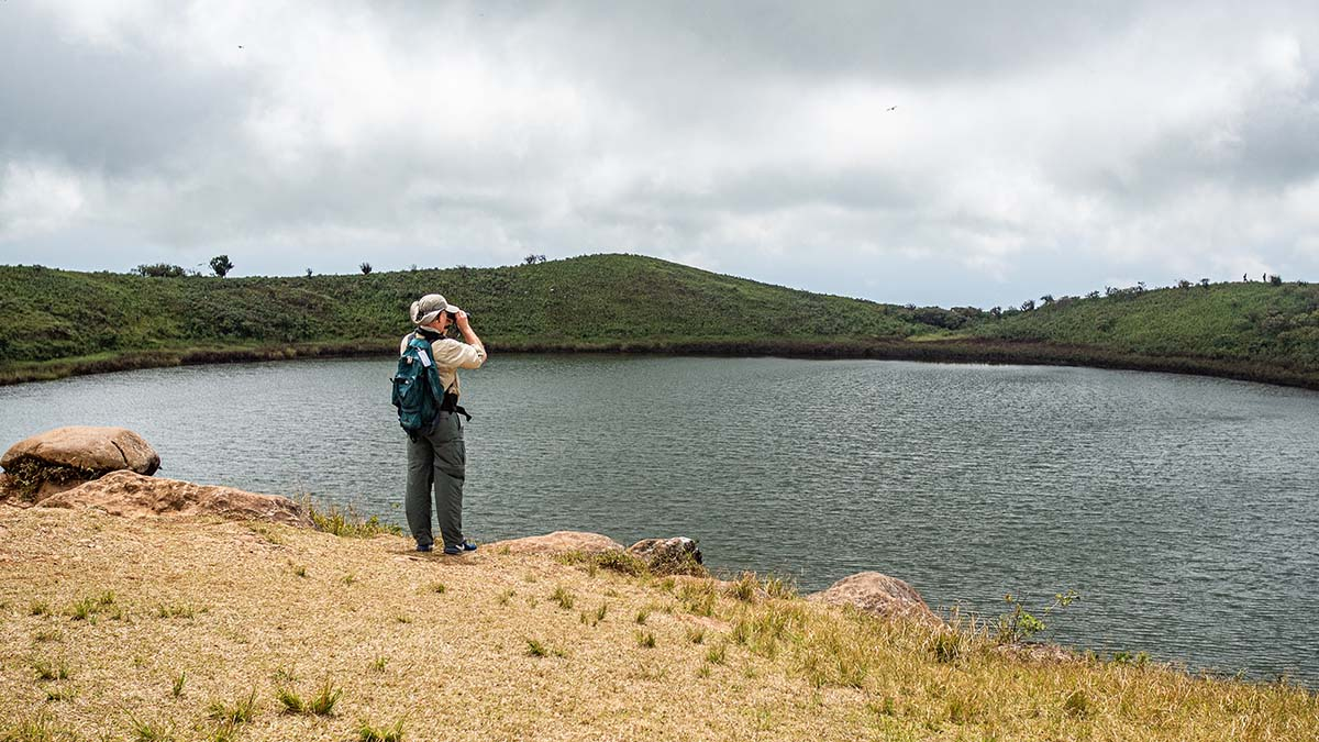 A man with a backpack and binoculars looks over a lagoon in the Galapagos.