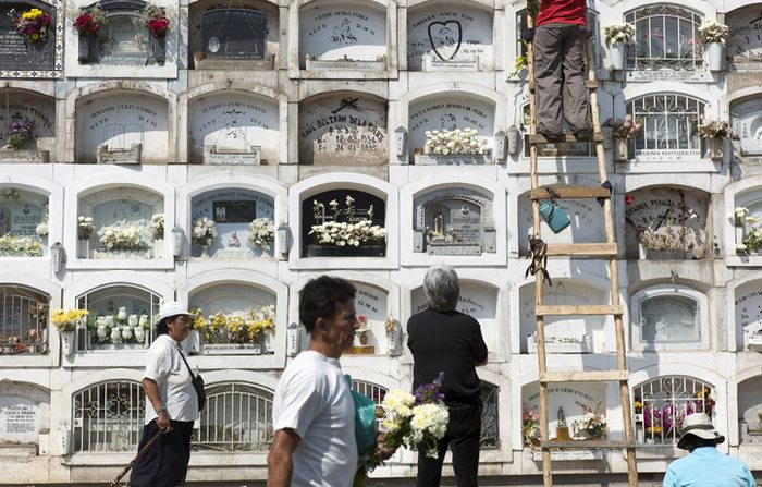 Peruvian families pay workers to place flowers and clean the hard-to-reach burial sites of their mothers at The Angel Cemetery on Mother's Day.