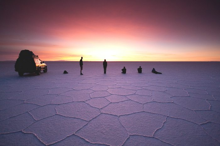 Silhouettes of a car and five travelers on the Uyuni salt flats at sunset.