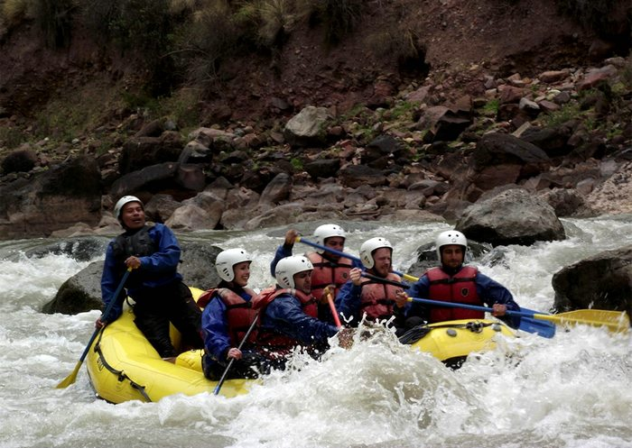 A group of people in helmets and life jackets river rafting on a yellow raft near large boulders.