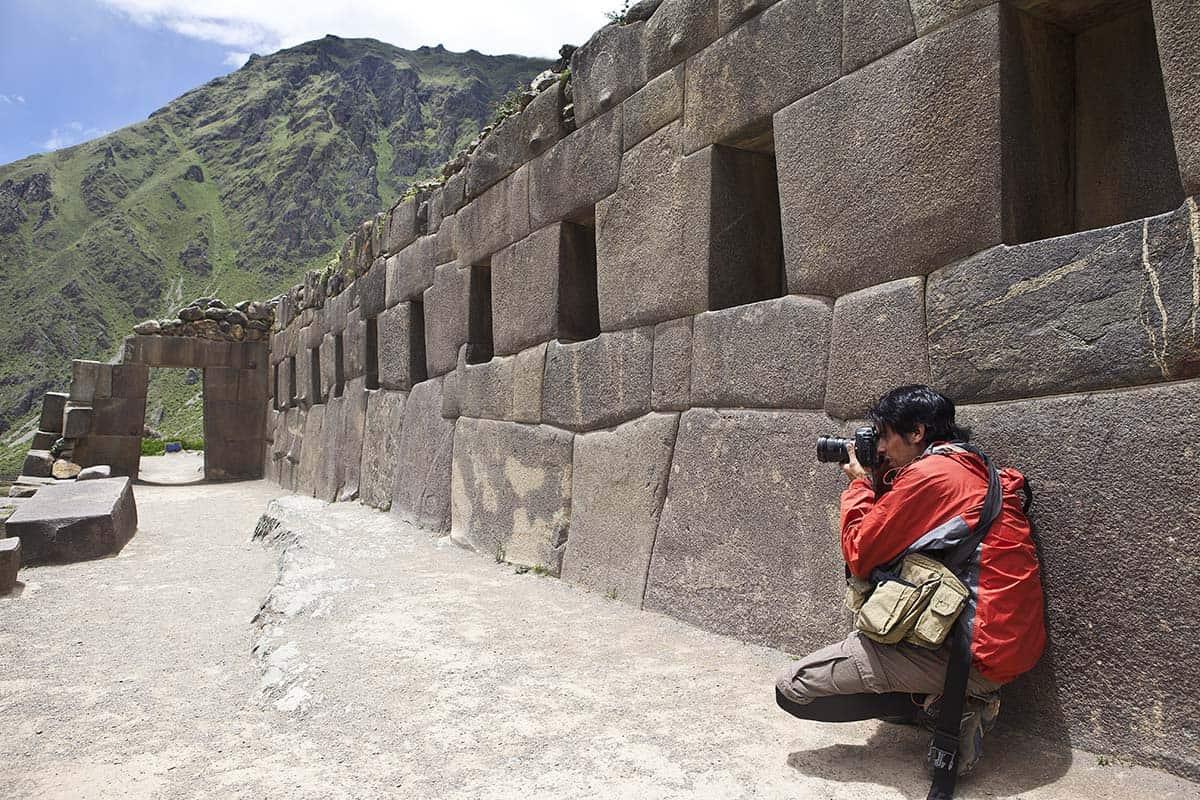 Photographer taking a photo at the Ollantaytambo ruins