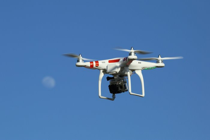 A white drone with red accents and a black camera flying in blue skies. A faint moon shape behind.