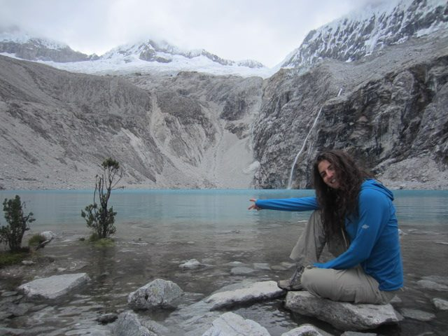 Liz poses in front of Lago 69 after trekking in Huaraz, Peru