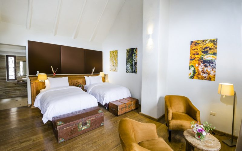 Adobe junior suite with white walls, two twin beds, wood floors, and yellow decor.