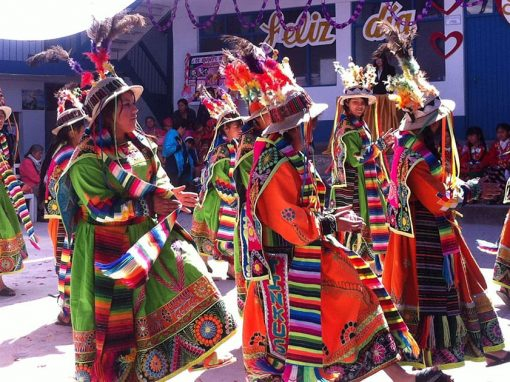 Dancers wearing colorful traditional clothing and performing a traditional dance in Cusco.