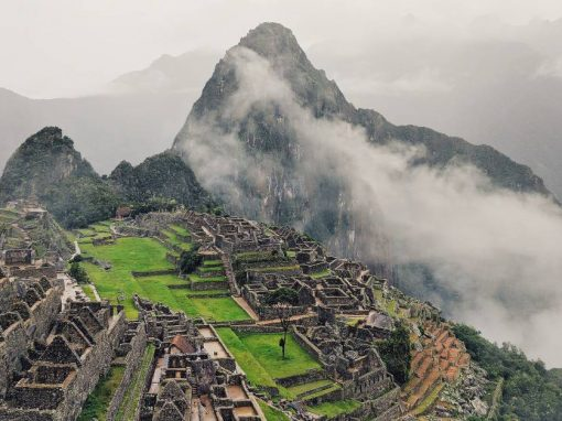 Machu Picchu and the surrounding mountains, with a blanket of fog rolling in from below.