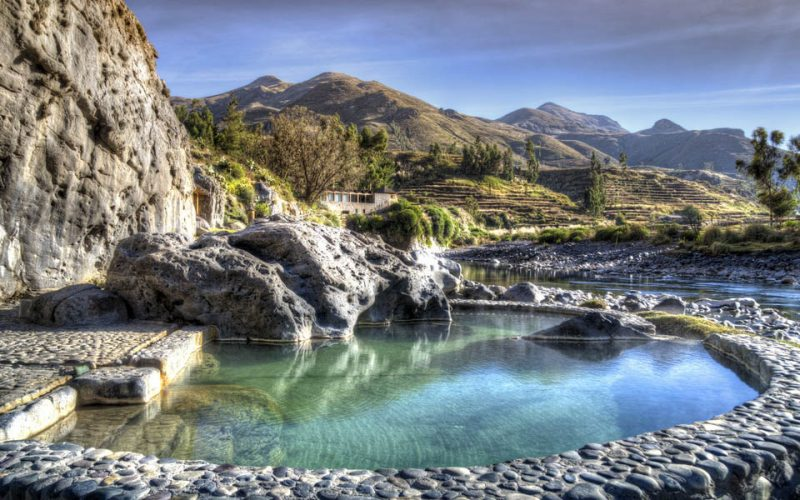 Turquoise natural hot springs with stone walls at the Colca Lodge.