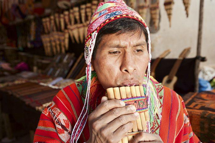 man playing a siku (panpipe) in Pisac market