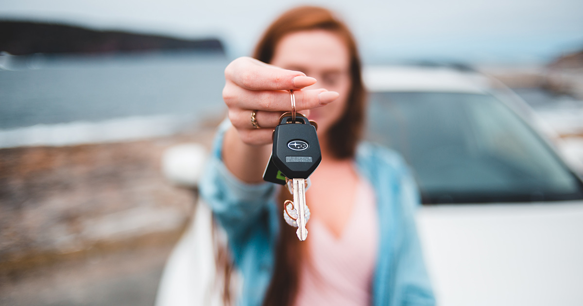 Set of keys in focus with woman and car blurred in background.