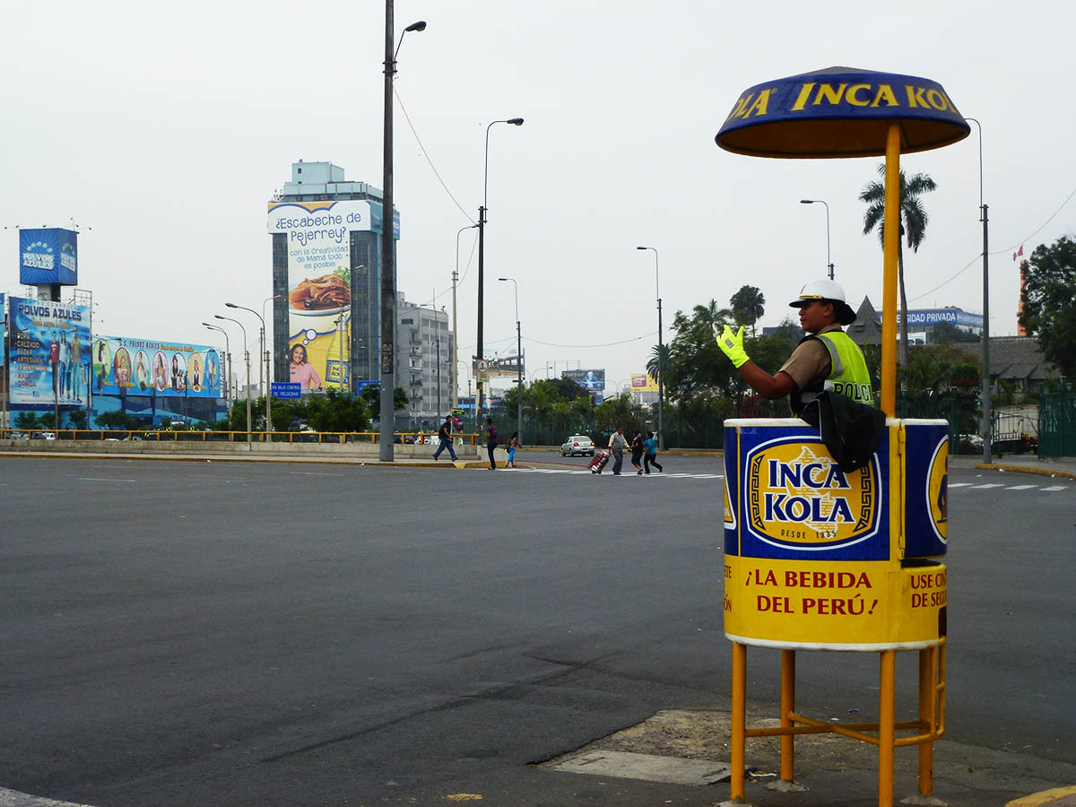 Transit officer directing traffic from a raised platform at an intersection in Lima.