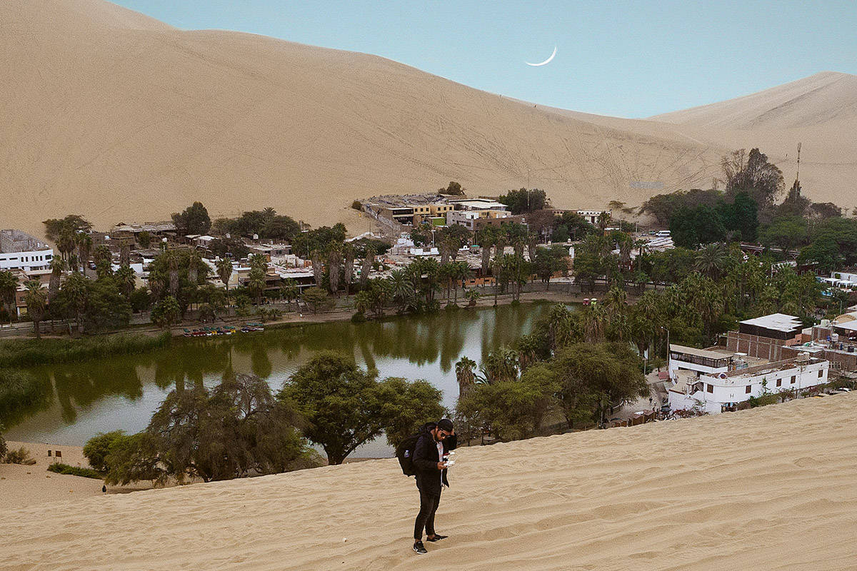 A man walking in the sand in front of the Huacachina Oasis