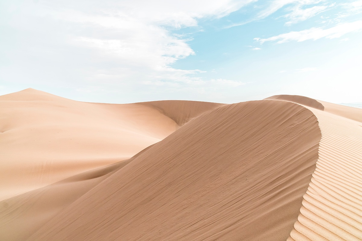 Sand dunes in the Peruvian desert with a cloudy blue sky backdrop.