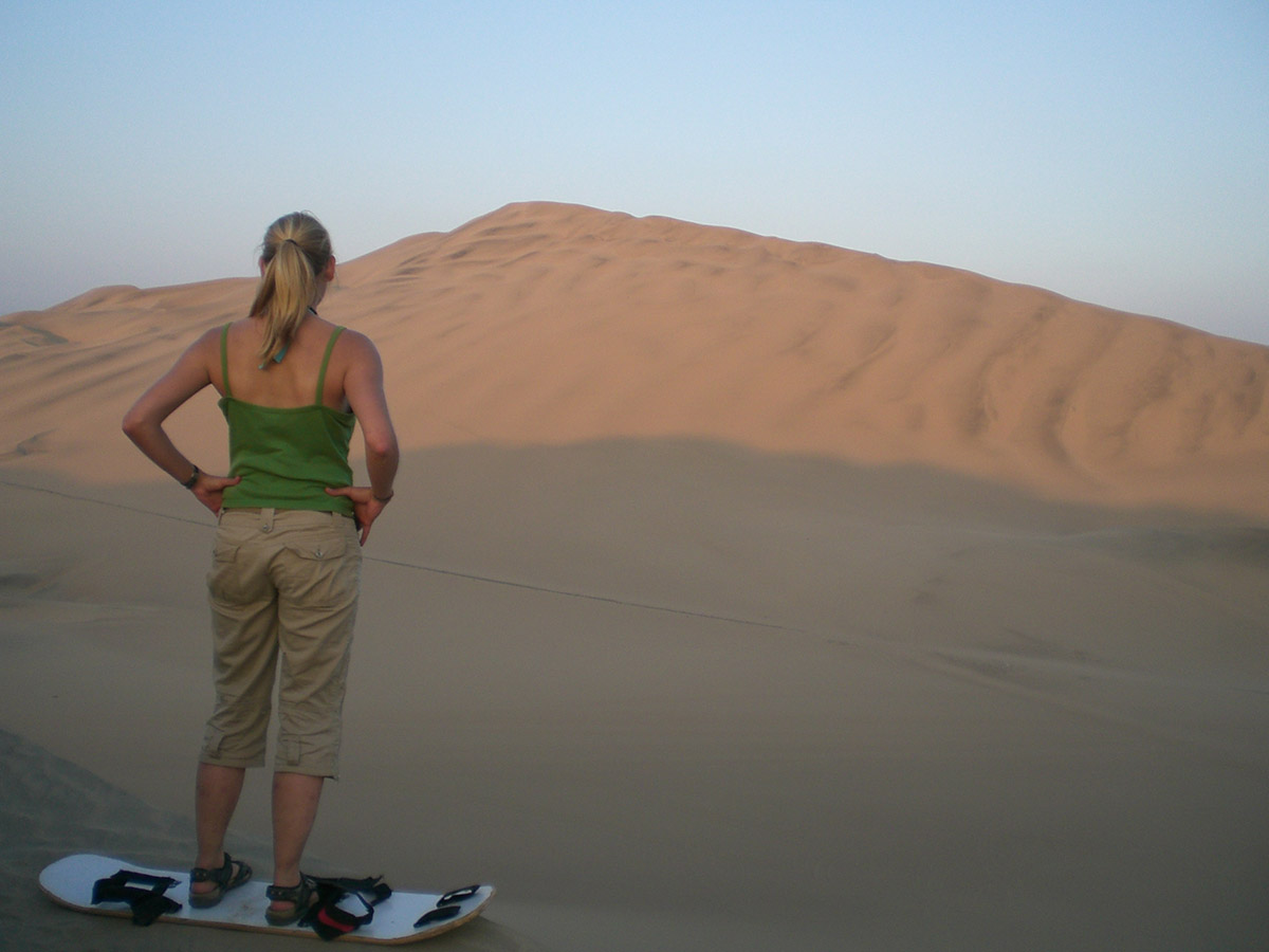 Woman with a sandboard at the sand dunes near Huacachina