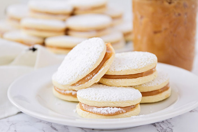 A circular white plate of fresh, stacked alfajores, with more alfajores blurred in the background.
