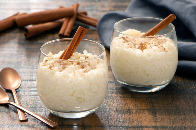 2 dessert cups of arroz con leche with cinnamon sticks.