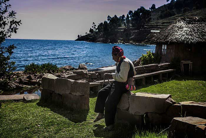 A man from the Island of Taquile weaving a piece of cloth, Lake Titicaca