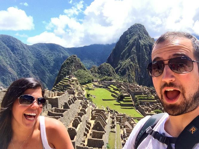 A selfie of two travelers in front of the Machu Picchu ruins.