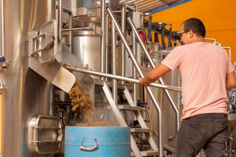 A worker emptying grain from a machine at Cerveceria del Valle Sagrado in the Sacred Valley.